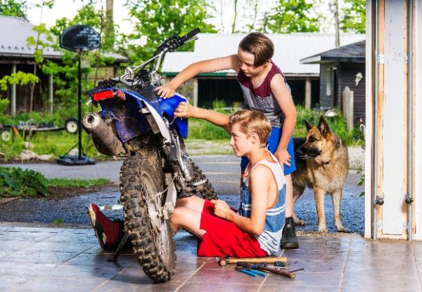 Young boys in a garage with a motocross